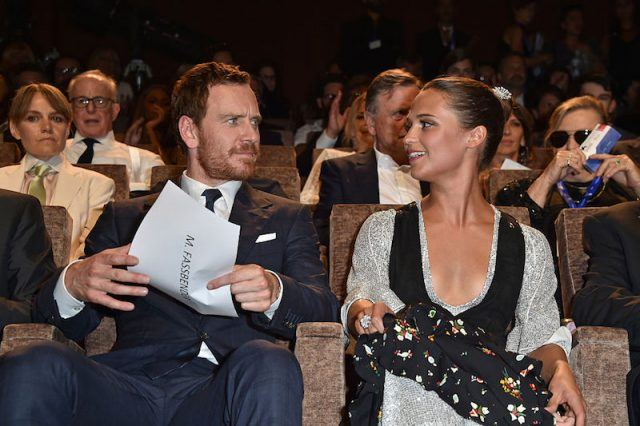 Alicia Vikander and Michael Fassbender sitting in a theatre together.
