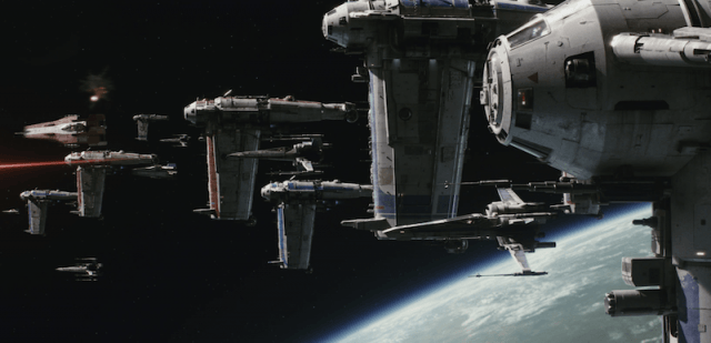 Space ships seen cruising past a planet in space.