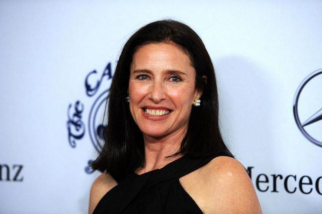 Mimi Rogers smiling while wearing a black dress and diamond earrings.