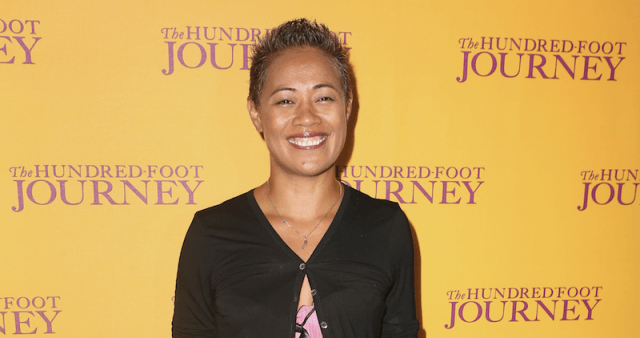 Monica Galetti stands in a black cardigan behind a yellow backdrop.
