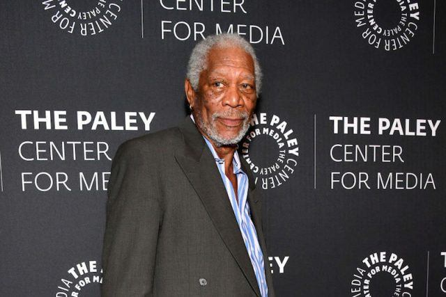 Morgan Freeman poses on a red carpet in a gray blazer and stares straight ahead.