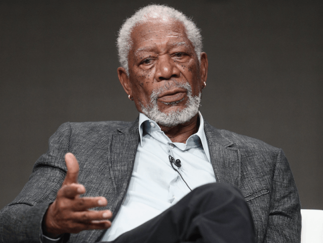 Morgan Freeman sitting on a white couch and waving his hand as he answers questions during a media panel.
