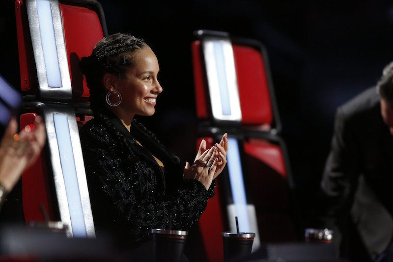 Alicia Keys sits in a red chair and claps her hands on The Voice