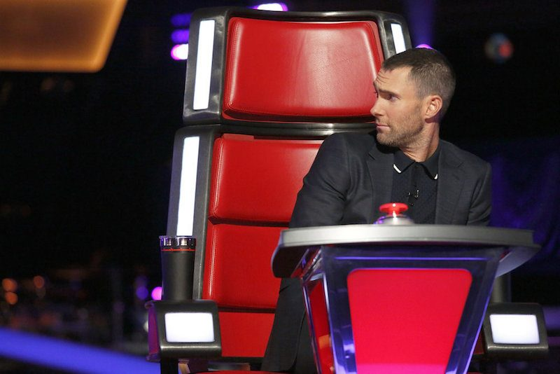 Adam Levine sits in a red chair on The Voice and looks to the side