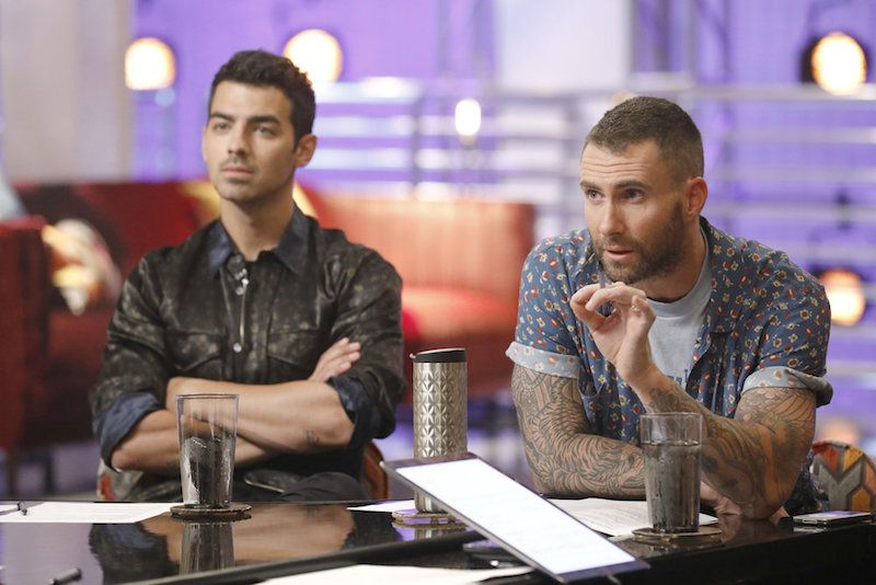 Adam Levine and Joe jonas gesture with their hands while sitting next to each other