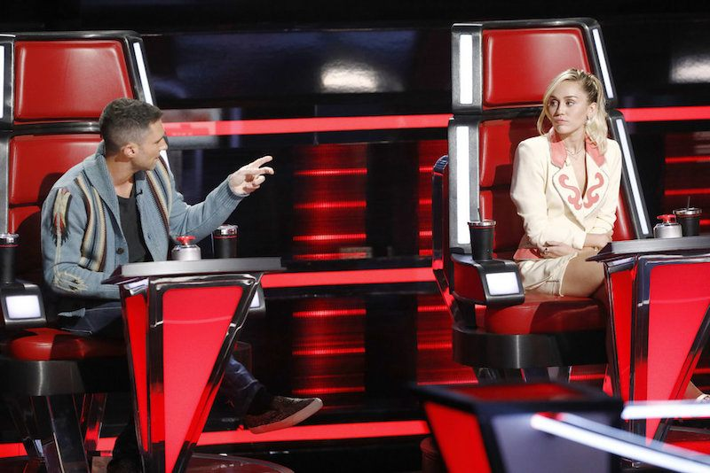 Adam Levine and Miley Cyrus sit next to each other in red chairs on The Voice