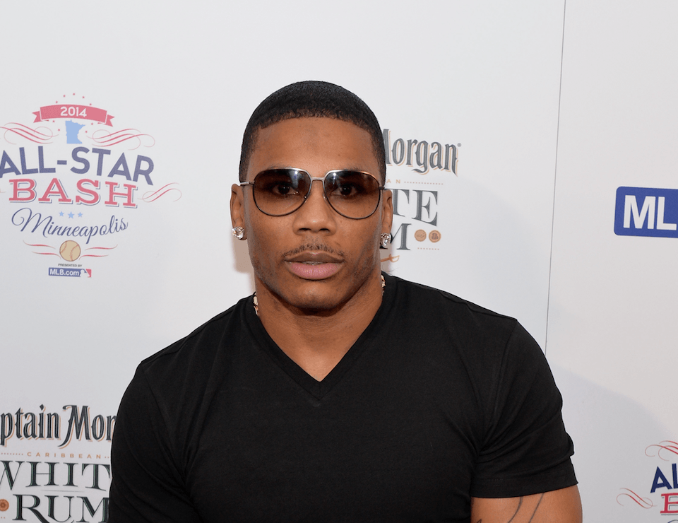 Nelly on the red carpet, wearing tinted sunglasses
