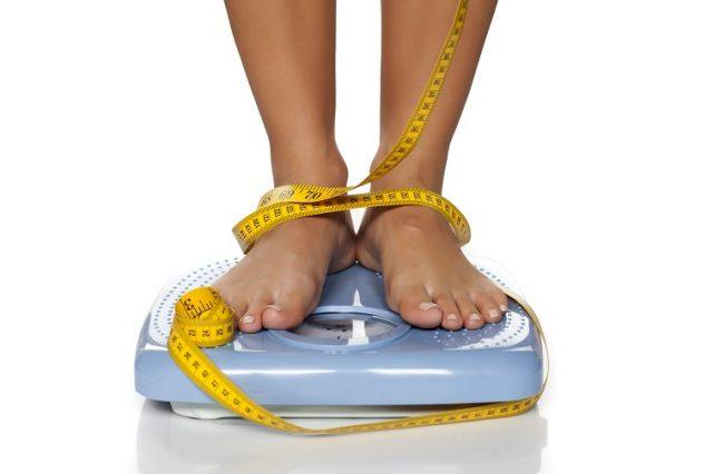 Woman weighing herself with tape measure around her ankles