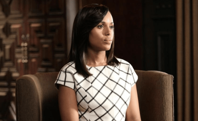 Olivia Pope sits in a brown chair while wearing a black and white patterned dress.