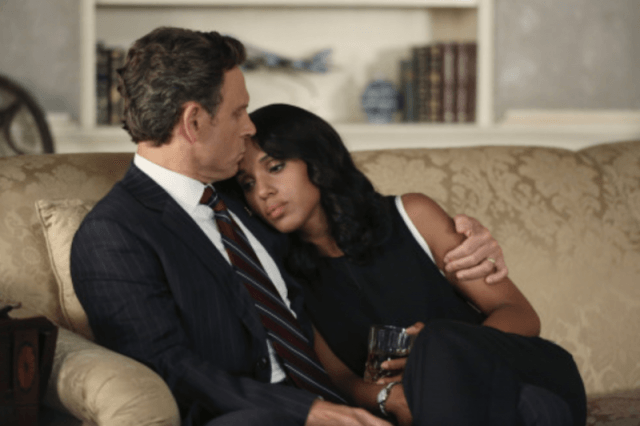 Olivia and Fitz sit on a couch together as he wraps his arm around her and she holds a glass.