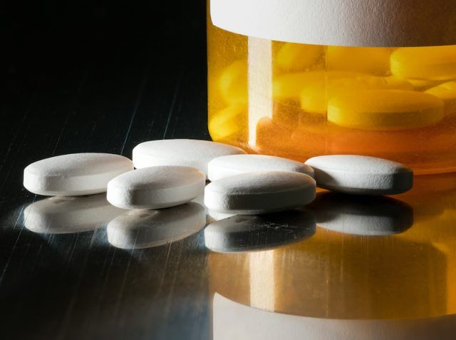 Large white pills outside an orange and white prescription pill bottle.