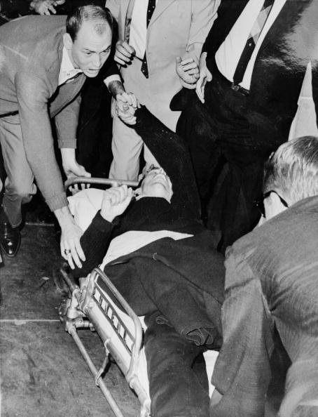 Lee Harvey Oswald is hurried into an ambulance after being shot