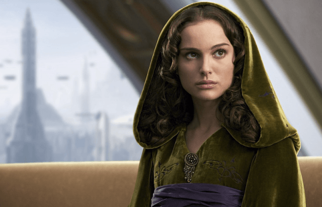 Padme sitting on a couch while wearing a green hood.