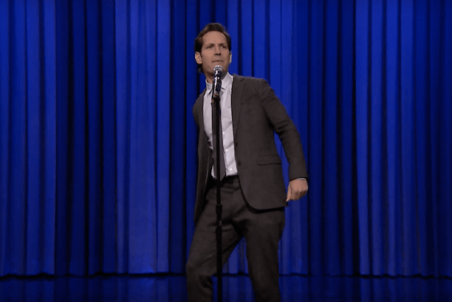 Paul Rudd singing and performing on stage in front of a blue curtain.