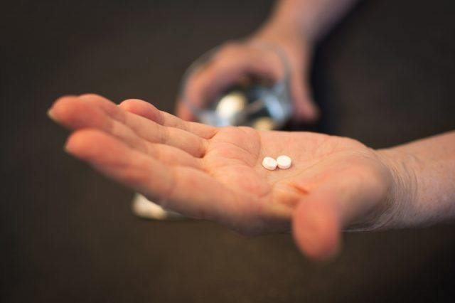 A person holds two small pills in their hand.