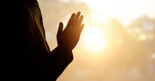 A person in a prayer position in sunlight.