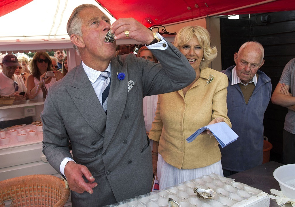 Prince Charles samples an oyster as Camilla, the Duchess of Cornwall, looks on.