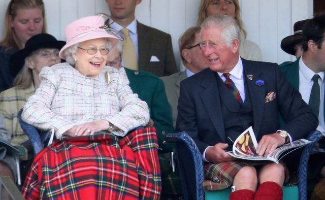 The Queen sits next to Prince Charles, who is laughing in her direction.