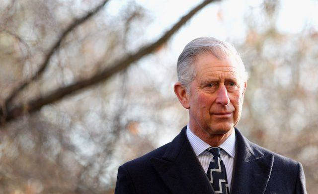 Prince Charles standing in front of trees in England .