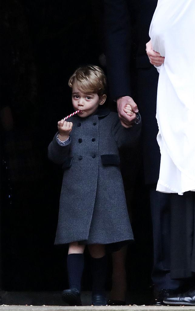 Prince George of Cambridge eats a sweet.