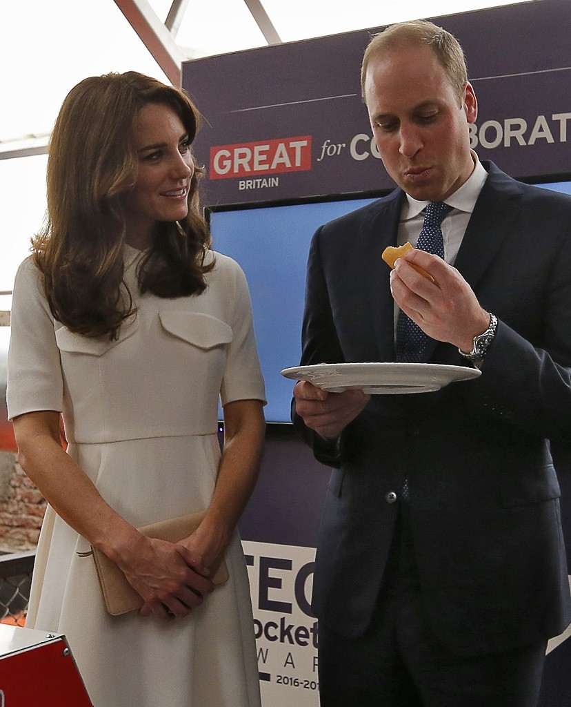 Prince William, Duke of Cambridge, eats traditional Indian food as his wife Catherine, Duchess of Cambridge looks on.