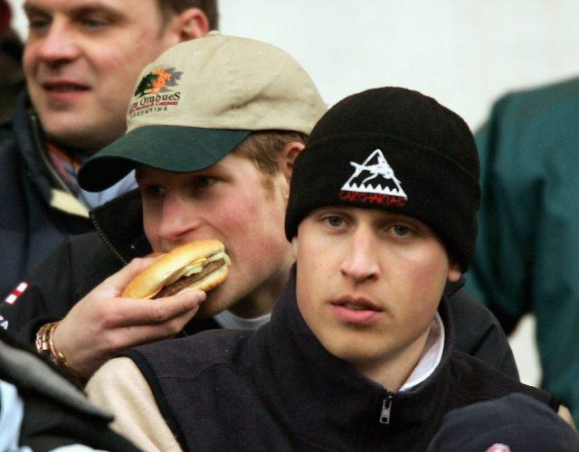Princes Harry eats a burger while Prince William watches on during the IRB Rugby Aid Match between The Northern Hemisphere and The Southern Hemisphere at Twickenham Stadium on March 5, 2005 in Twickenham, England. (Photo by David Rogers/Getty Images)