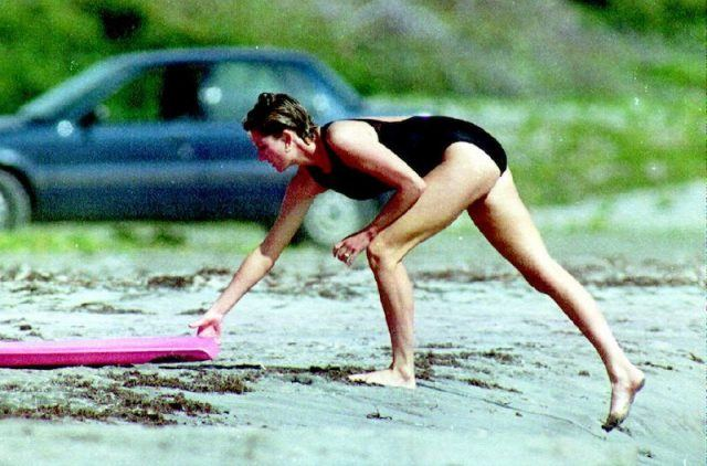 Princess Diana reaching for a surfboard.