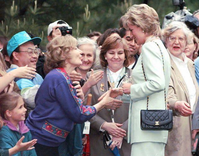Princess Diana greeting fans and shaking hands with people in a crowd.