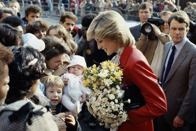 Princess Diana greeting fans and holding flowers.