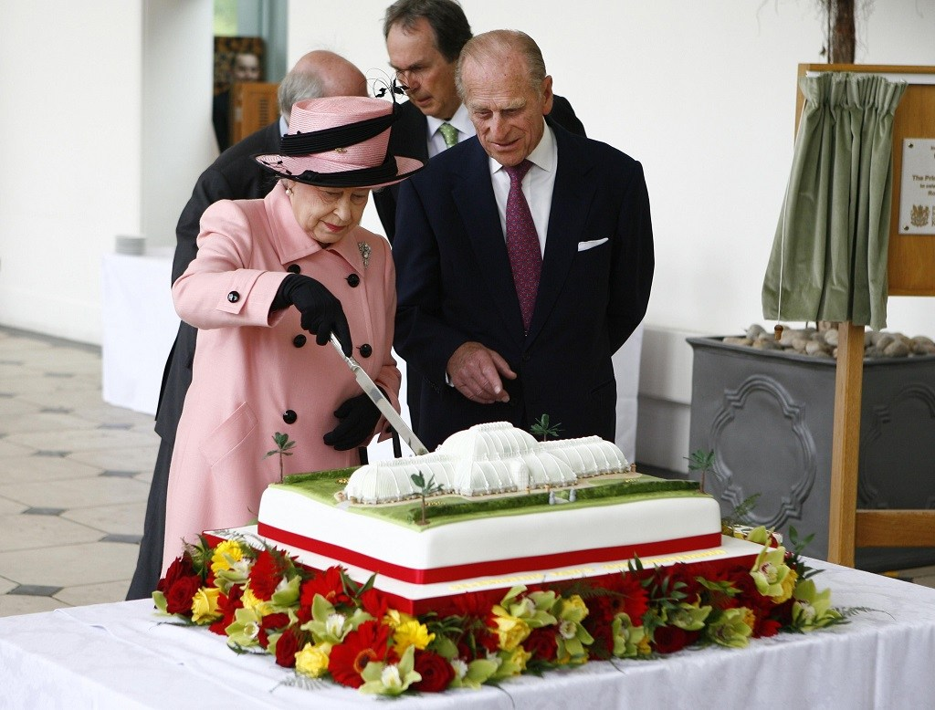 Queen Elizabeth II cuts a cake as Prince Philip looks on.