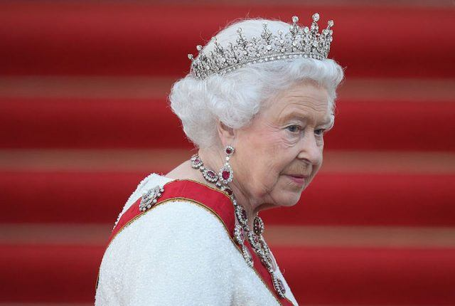 Queen Elizabeth II wearing a jeweled crown and red sash in front of bright red steps.