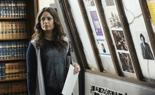 Quinn Perkins stands in front of a book shelf holding a sheet of paper.