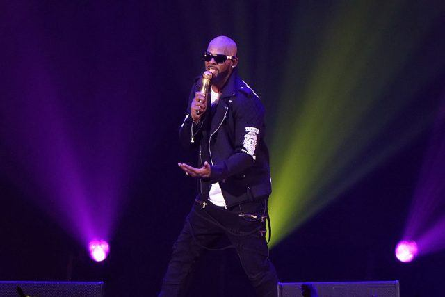 R.Kelly performing on stage while holding a microphone.