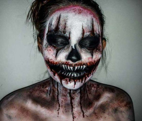 A woman wearing black, white, and red makeup to make her look like an evil clown