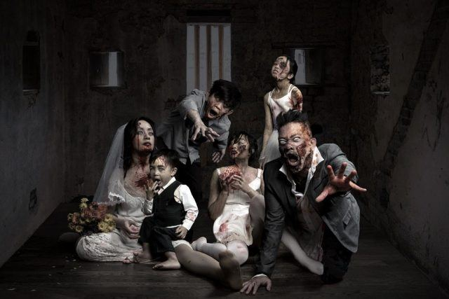 A family dressed in nice clothes wearing makeup to make them look like zombies