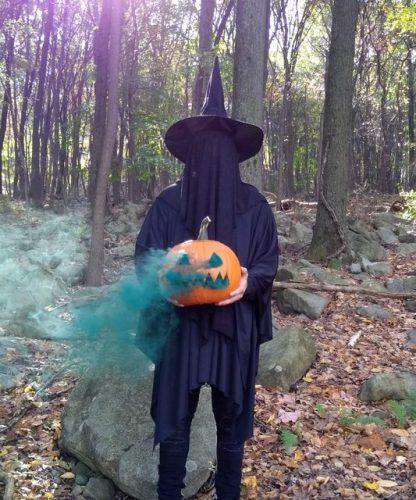 A man dressed in a black cloak, hat, and vail holding a jack-o-lantern that is spewing smoke