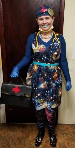 A woman wearing a galaxy print dress and holding a medical bag