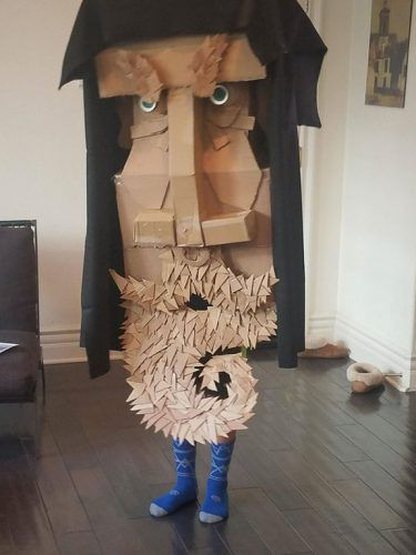 A man with a very large cardboard mask of an old wise man
