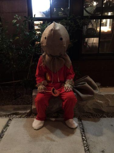a person wearing a red jumpsuit with a burlap sack on their head