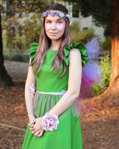 lady in a green dress with make made to make her look like an elf