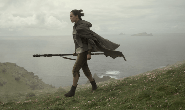 Rey walks holding her weapon alongside a cliff.