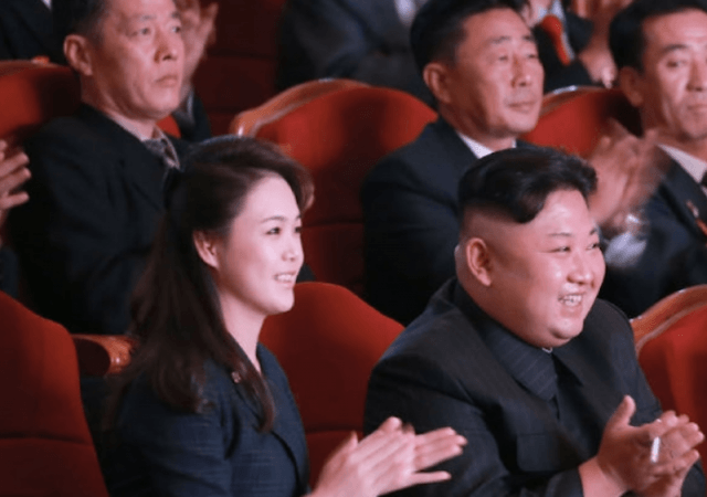 Kim Jong Un sits and applauds with his wife.