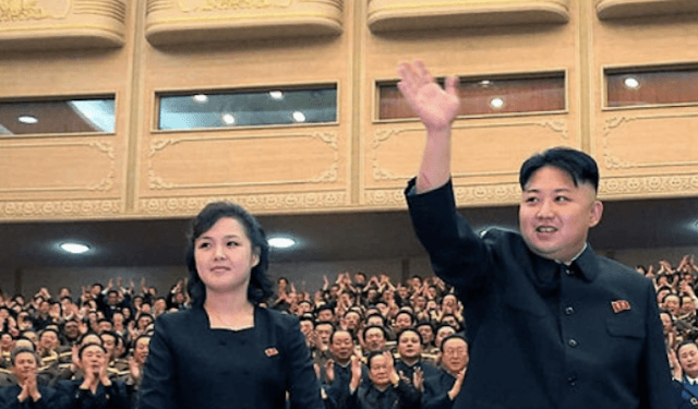 Kim Jong Un smiles and waves at a crowd as he stands next to his wife.