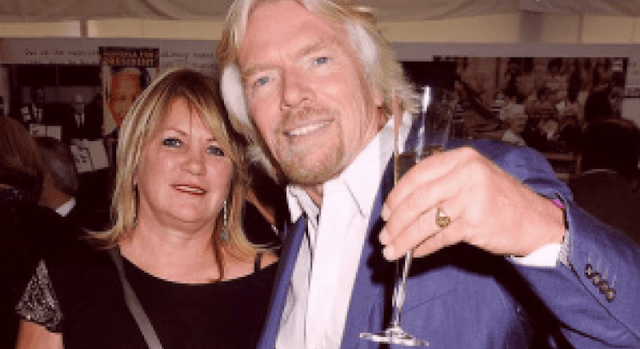 Kristen Tomassi and Richard Branson smiling thither as Branson holds up a glass of champagne.