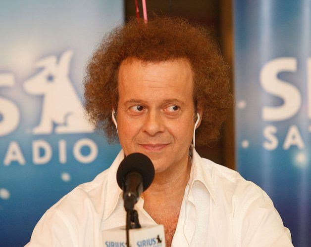 Richard Simmons sitting in front of a microphone while wearing headphones.