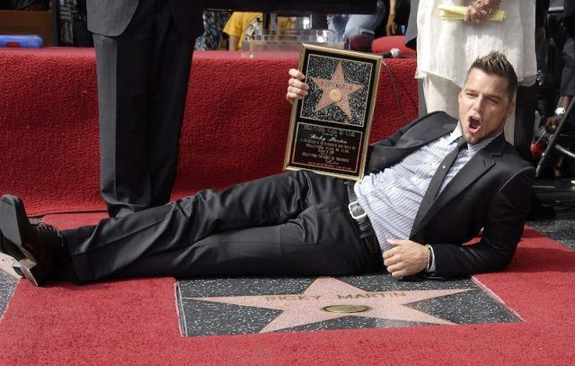 Ricky Martin posing with his star and plaque.