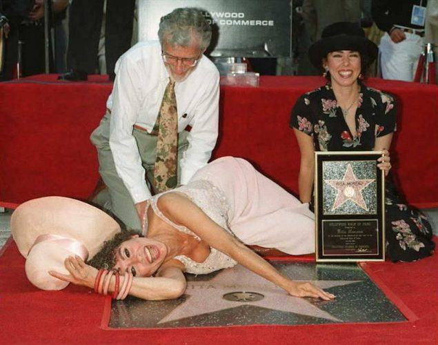 Rita Moreno lays on top of her star while her husband and daughter pose with her.