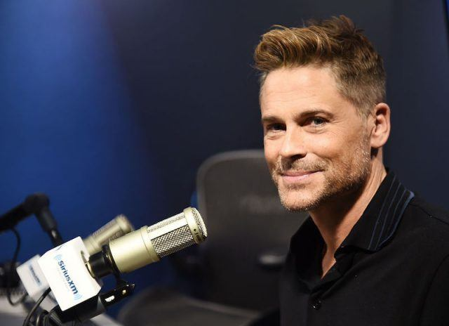 Rob Lowe sitting in front of a microphone and smiling.