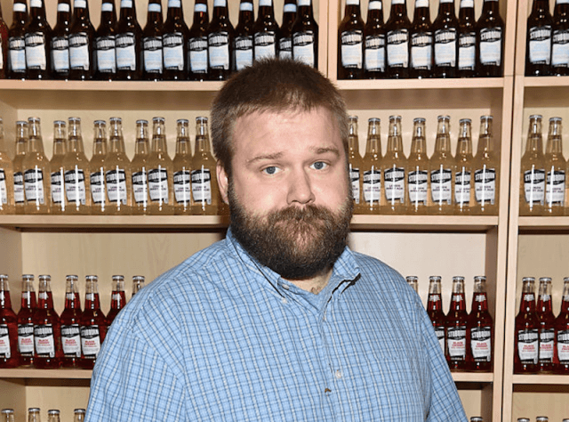 Robert Kirkman standing in front of glass bottles.