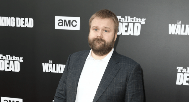 Robert Kirkman standing in a white shirt and plaid striped suit at a red carpet event.